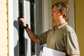 Parole reforms: Photo of a man with a clipboard knocking on a house door.
