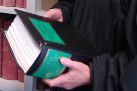 Sentencing reform: Photo of a judge in black robes holding a criminal law book.